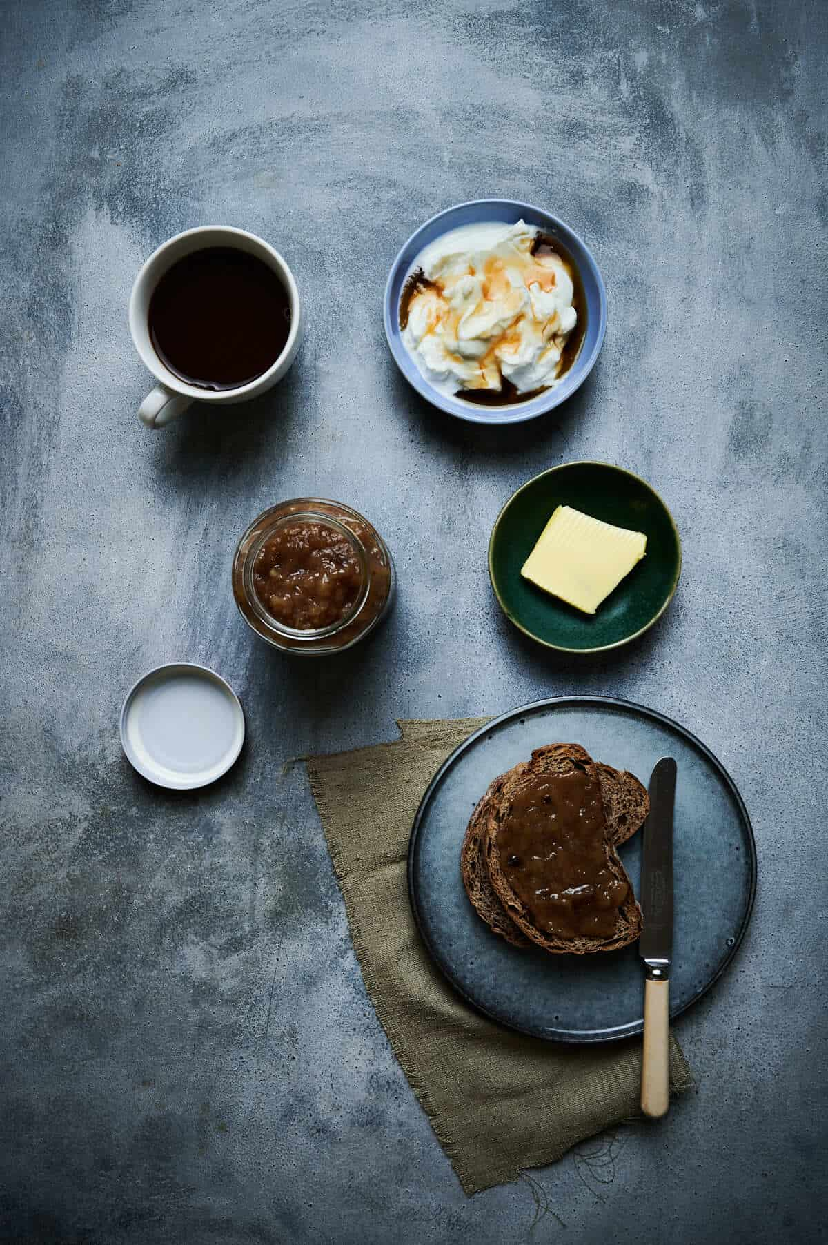 a grey table with toast, yogurt, butter , coffee and preserves