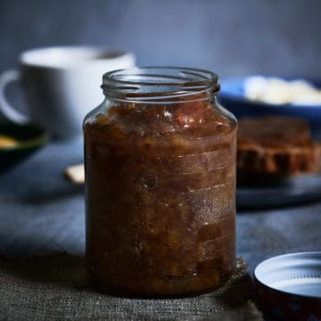 a jar of banana jam on a grey table