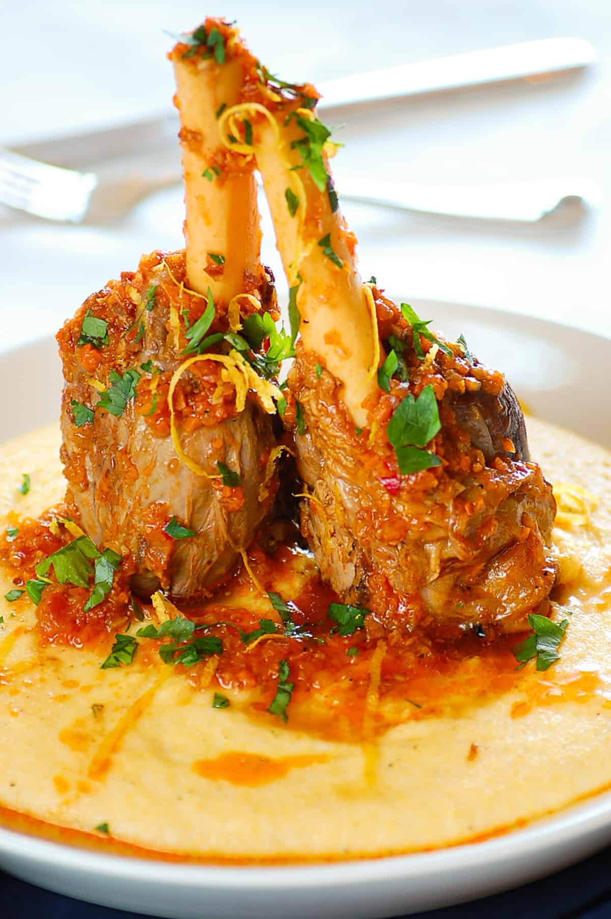 cooked lamb shanks served with soft polenta
