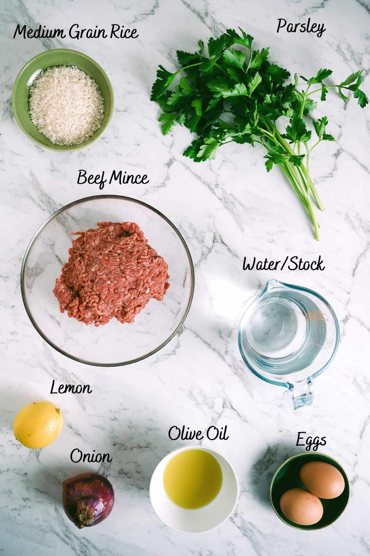 rice, parsley, ground beef, water, lemon, onion, olive oil and eggs laid out on a white table