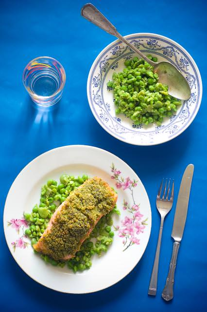 baked slamon with a herbed crust served with a side of crushed peas and broad beans
