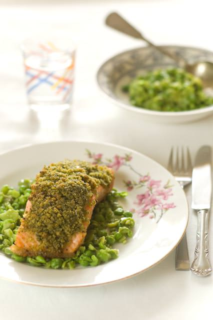 baked salmon with a herbed crust served with a side of broad beans and peas