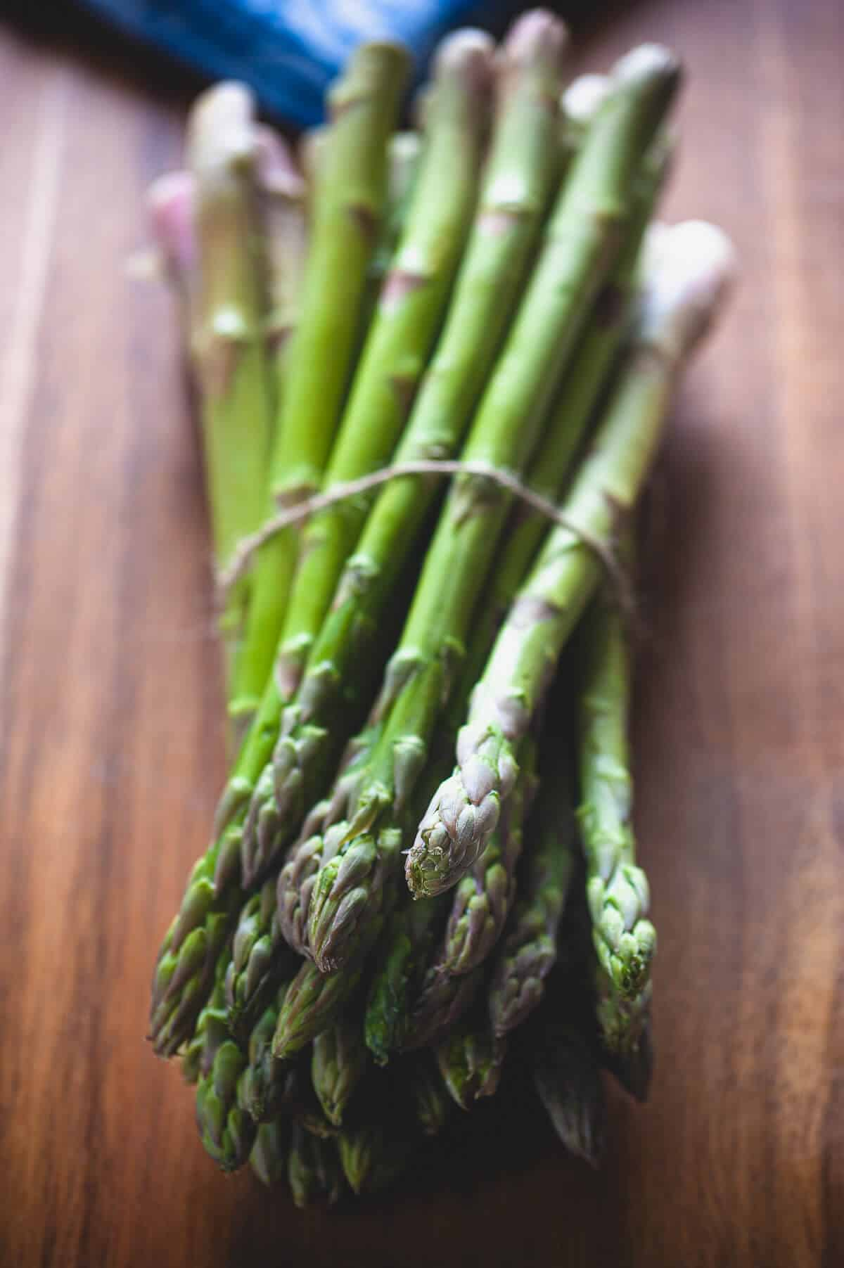 a bunch of asparagus on a wooden table