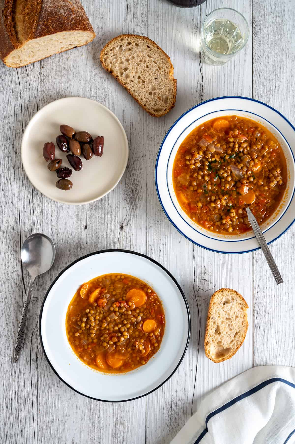 two bowls of lentil soup served on a white table with a side of olives and bread
