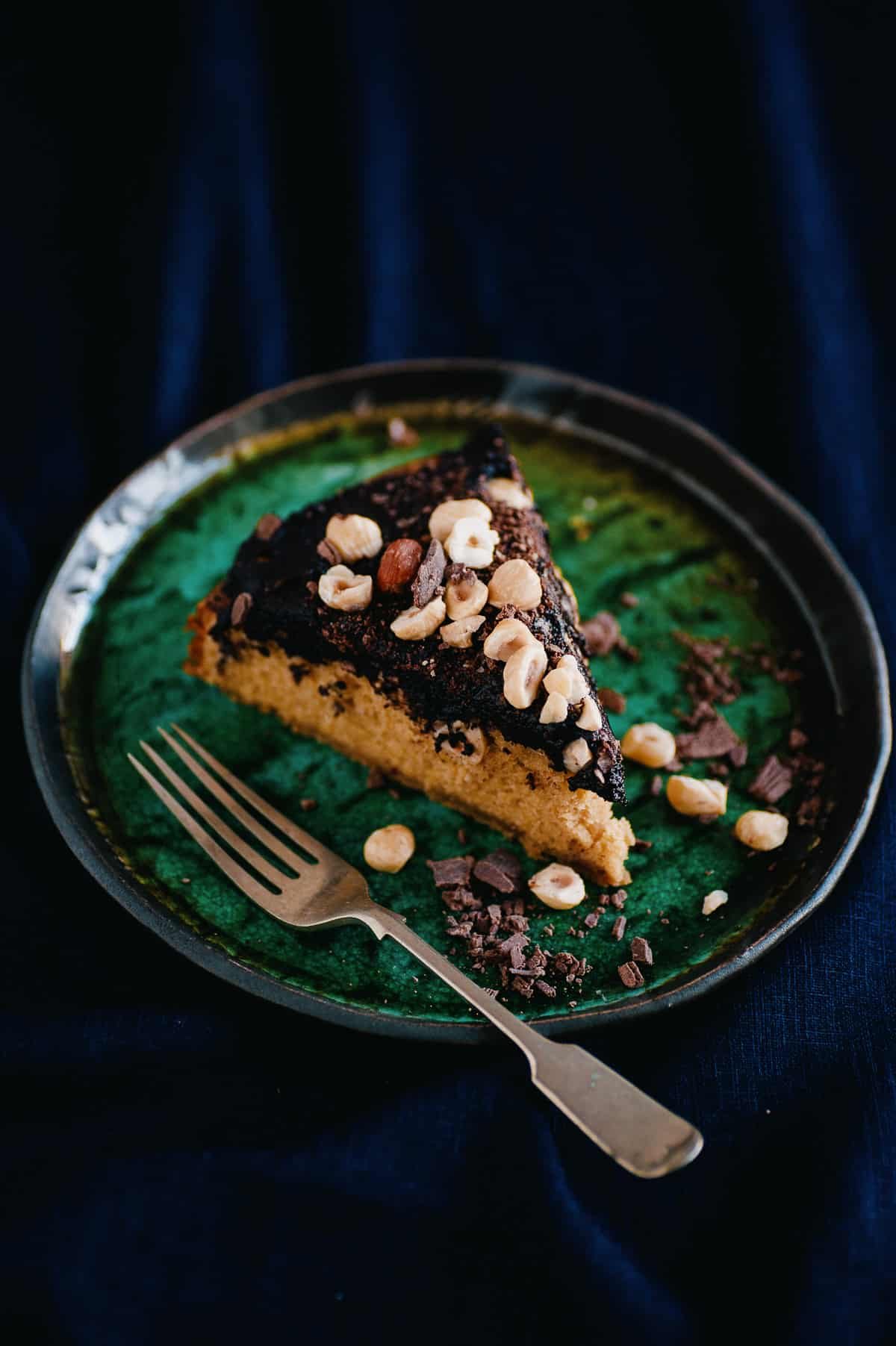 a slice of cake on a plate. the cake is covered in a chocolate spread and covered hazelnuts