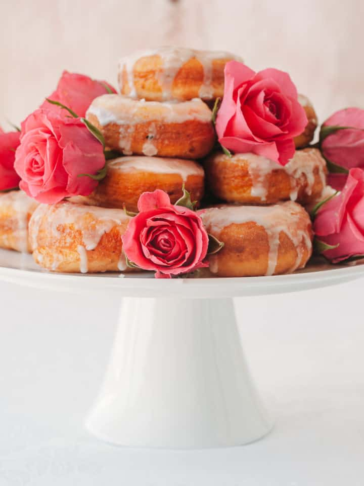 doughnuts piled high on a cake stand drizzled with icing and decorated with pink roses