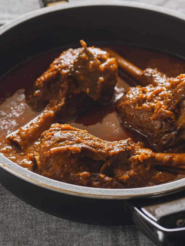 three braised lamb shanks in a black pan