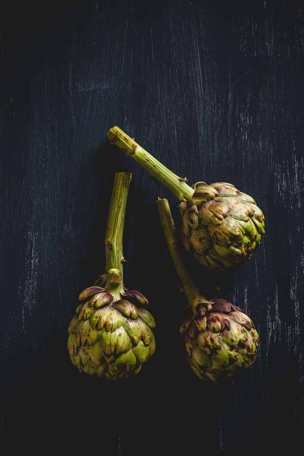 three artichokes on a table