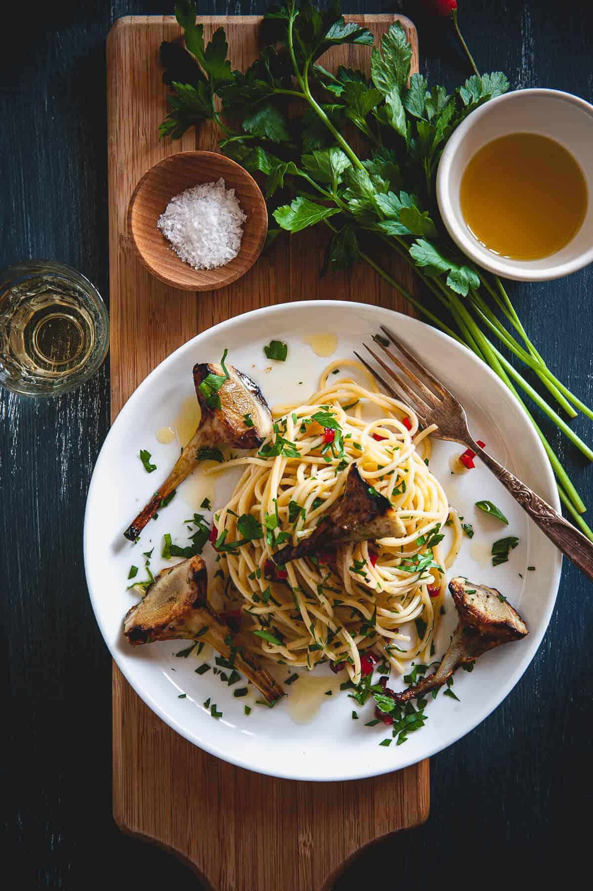 spaghetti with artichokes served in a plate on a board