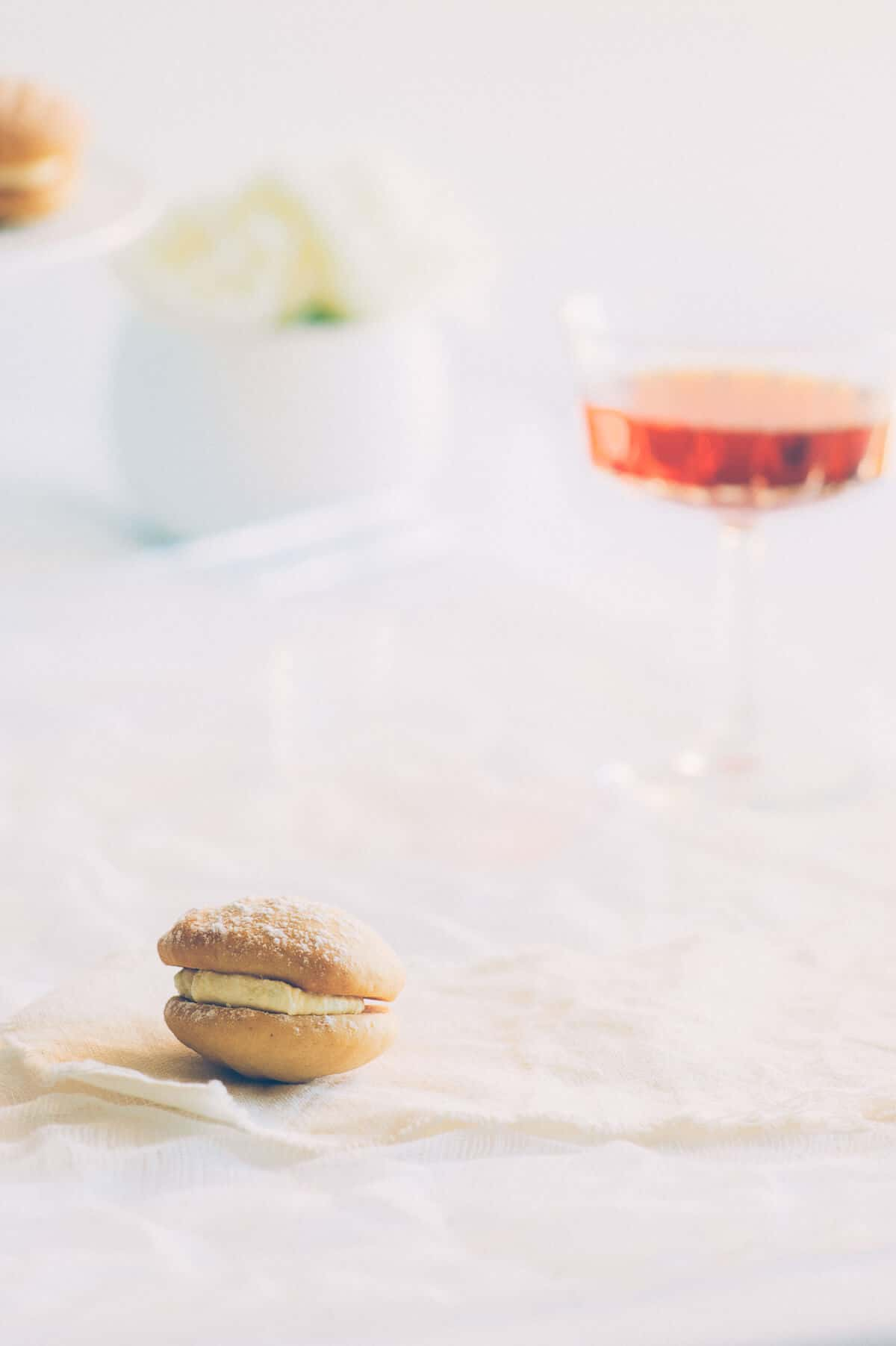 a cookie with a glass of wine presented in the background