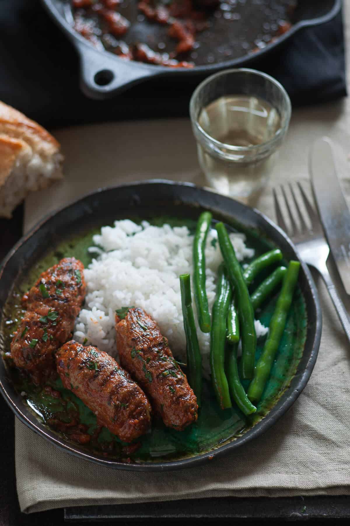 three oblong meatballs served on a plate with rice and green beans