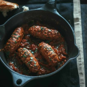 4 meatballs served in a pan with tomato sauce