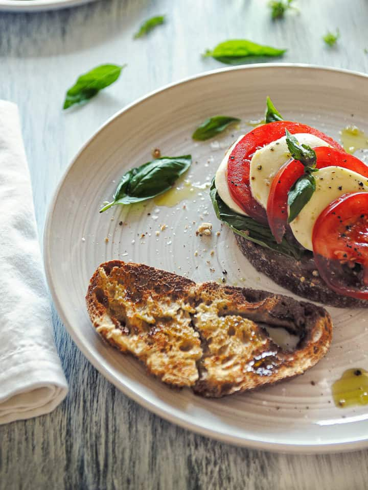 toasted bread on a plate topped with mozzarella cheese, tomatoes and basil