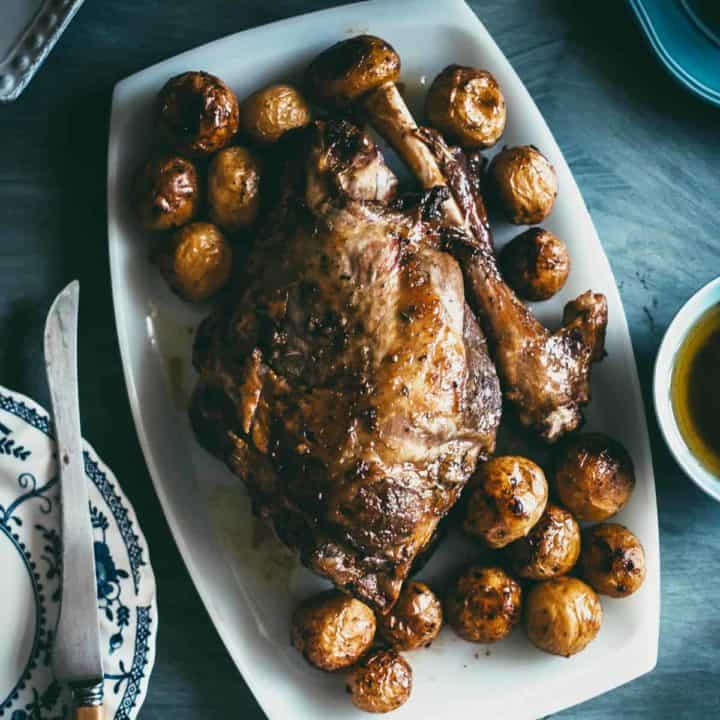 a top down view of Greek roast lamb served with roasted Greek potatoes on a white platter