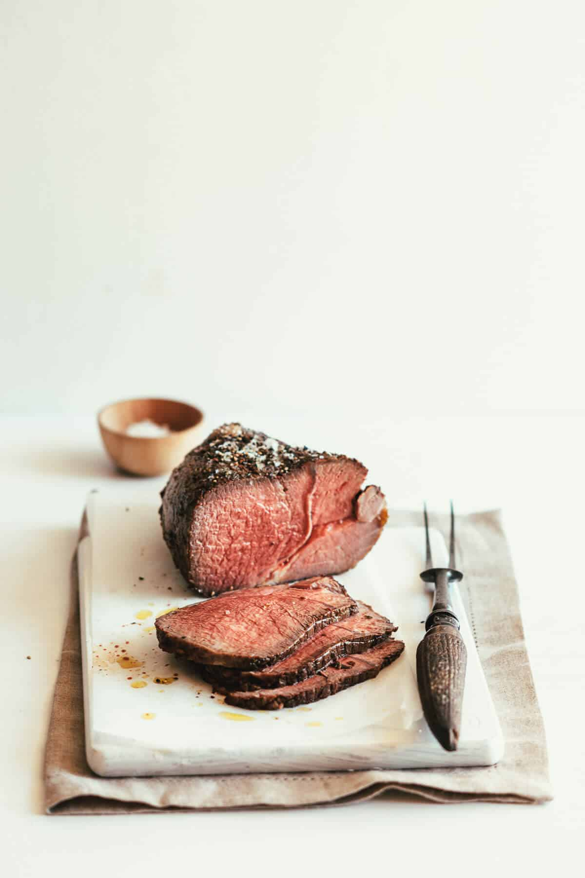sliced roast beef served on a white board