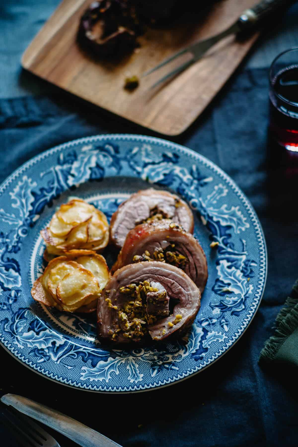 roast lamb served on a blue plate with a side of potatoes