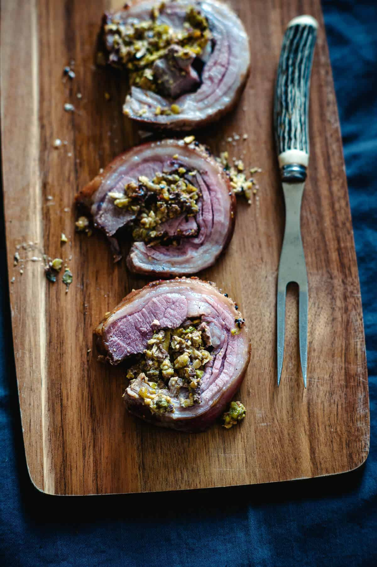 three slices of cooked lamb loin on a board