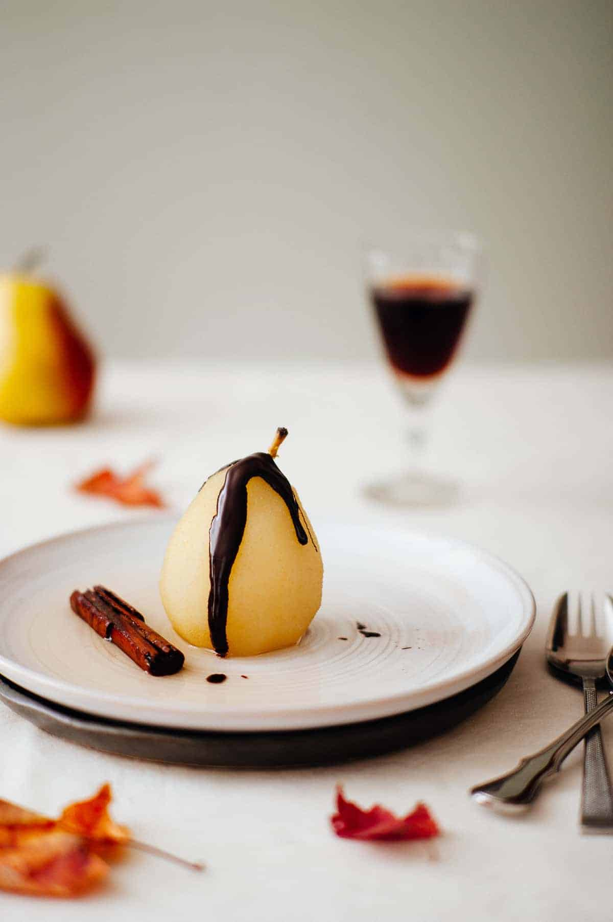 a poached pear on a plate drizzled with chocolate