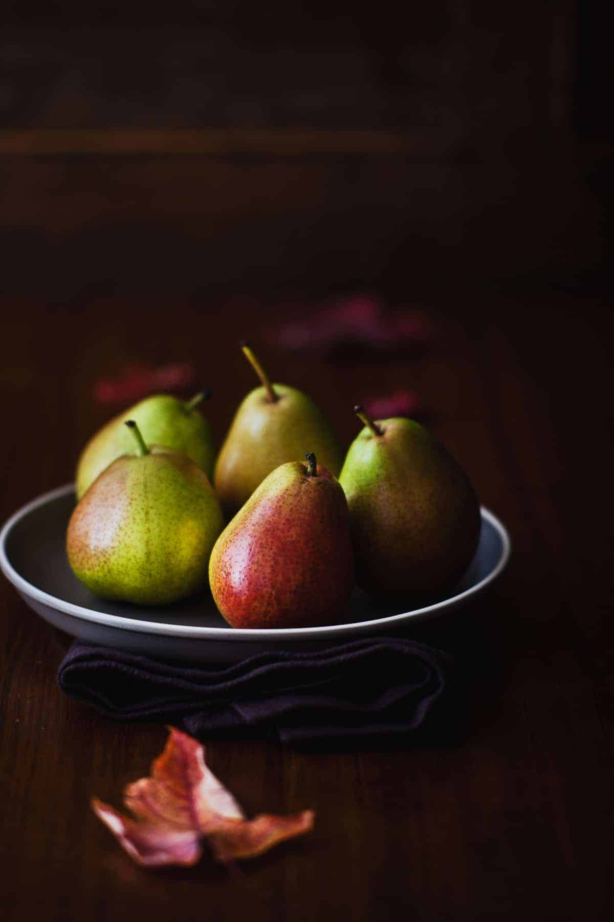 five pears on a grey plate