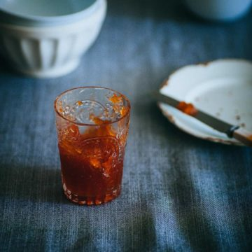 a glass filled with marmalade on a grey table