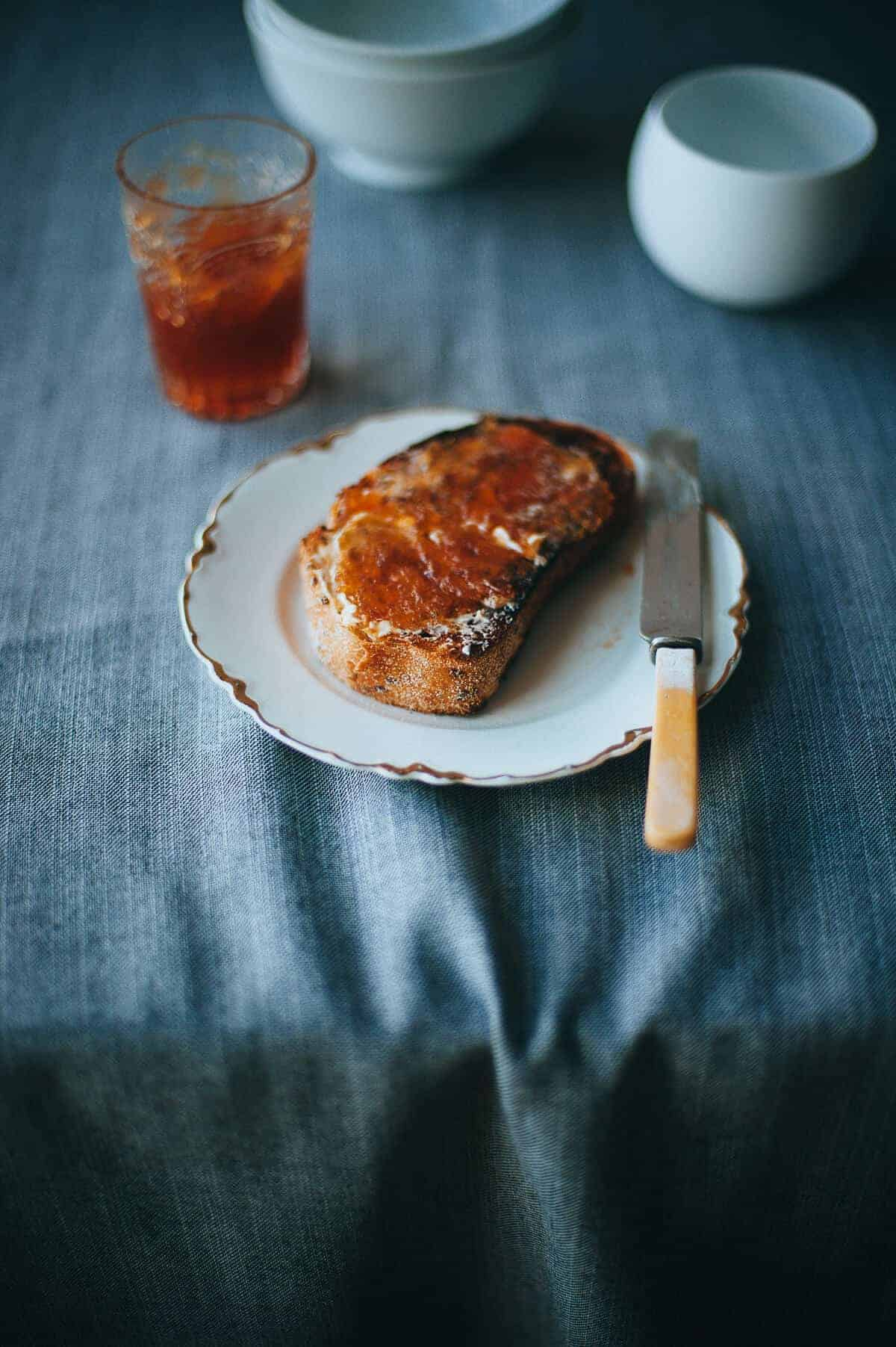 toasted bread on a plate smothered with butter and marmalade