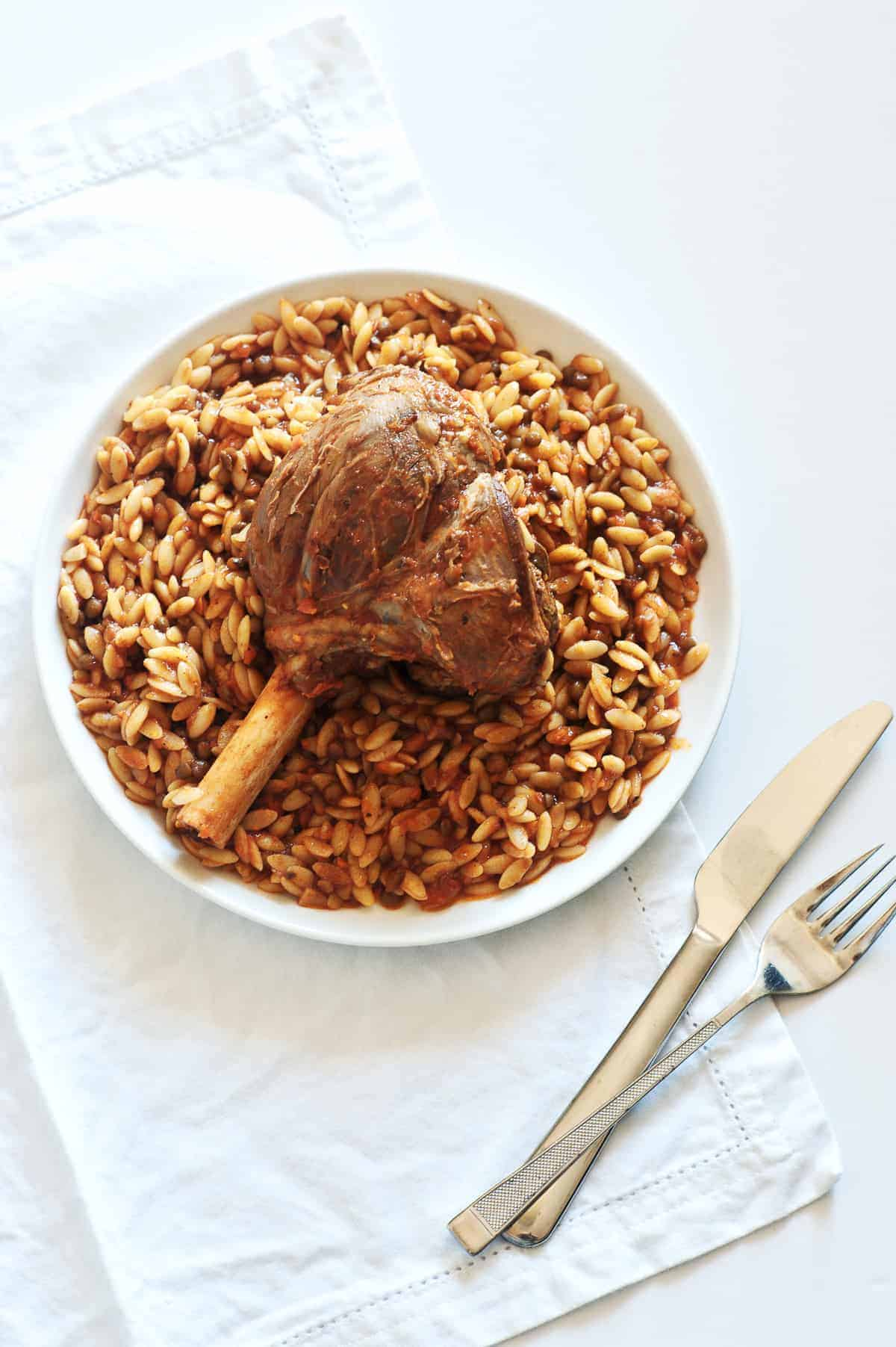 a birds eye view of a a braised lamb shank served with orzo pasta on a white plate
