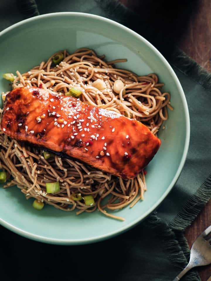 cooked salmon on a bed of soba noodles served in a green plate