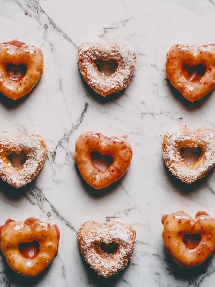 9 glazed heart-shaped doughnuts on a marble surface