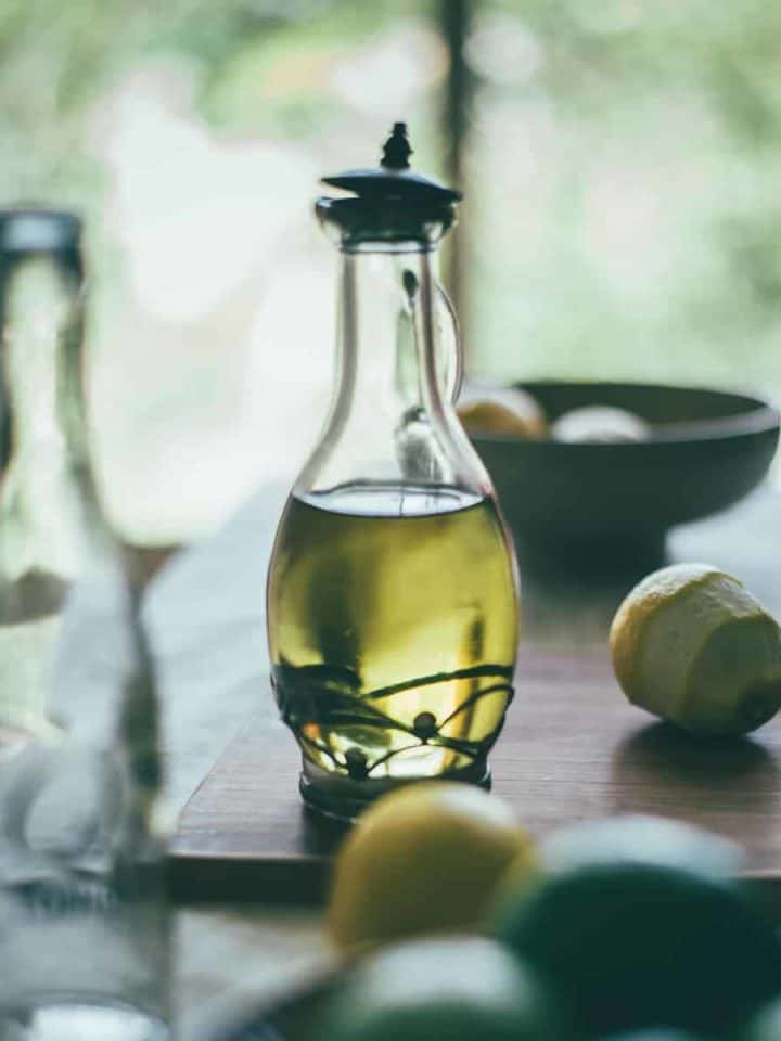 a bottle filled with olive oil on a table with peeled limes and lemons