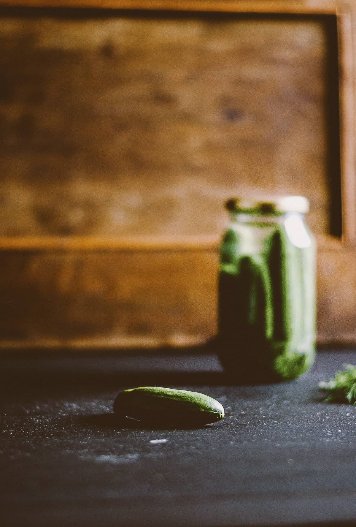 a glass jar full of pickles on a dark table with a wooden background