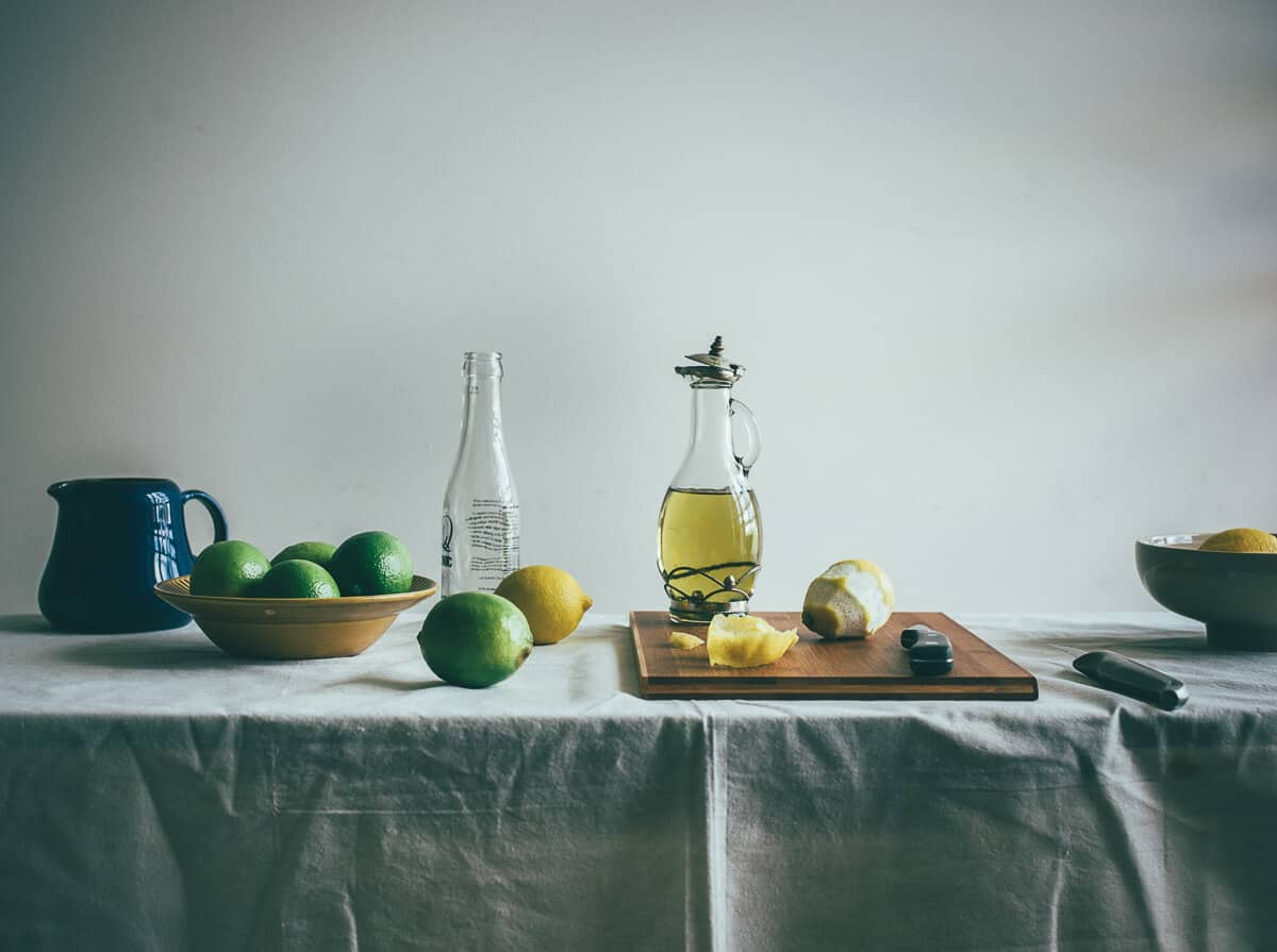 a table filled with lemons, limes and a bottle of olive oil