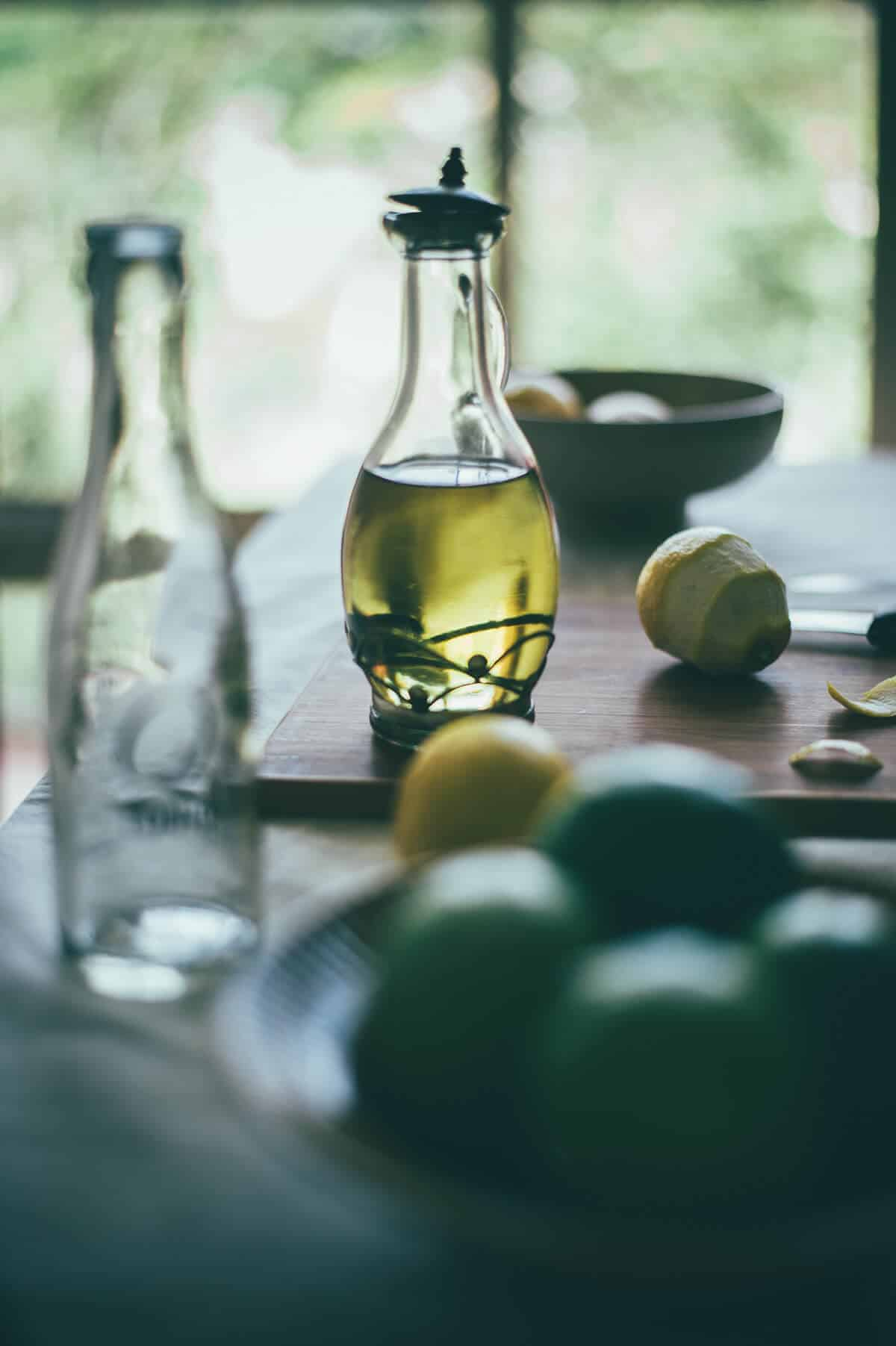 a bottle of olive oil with limes and lemons on a table