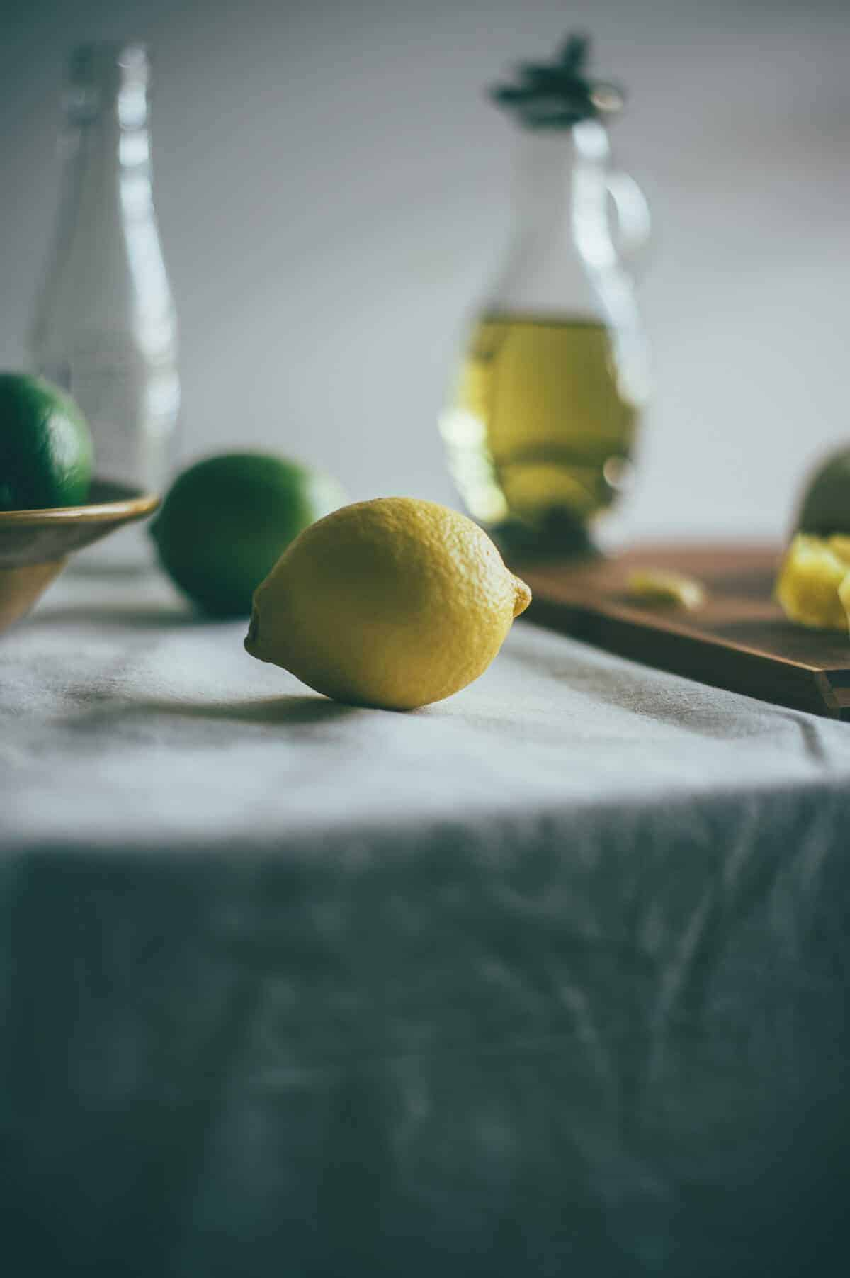 a whole lemon with limes on a table with a bottle of olive oil