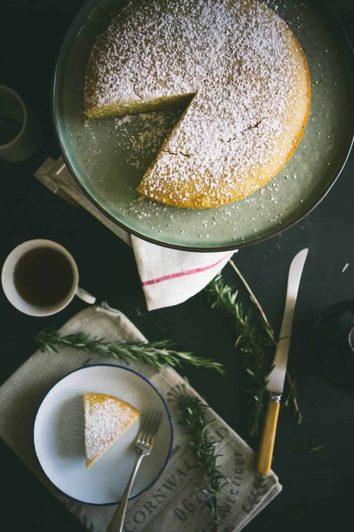 a birds eye view of a sliced cake with a cup of tea and a knife next to it