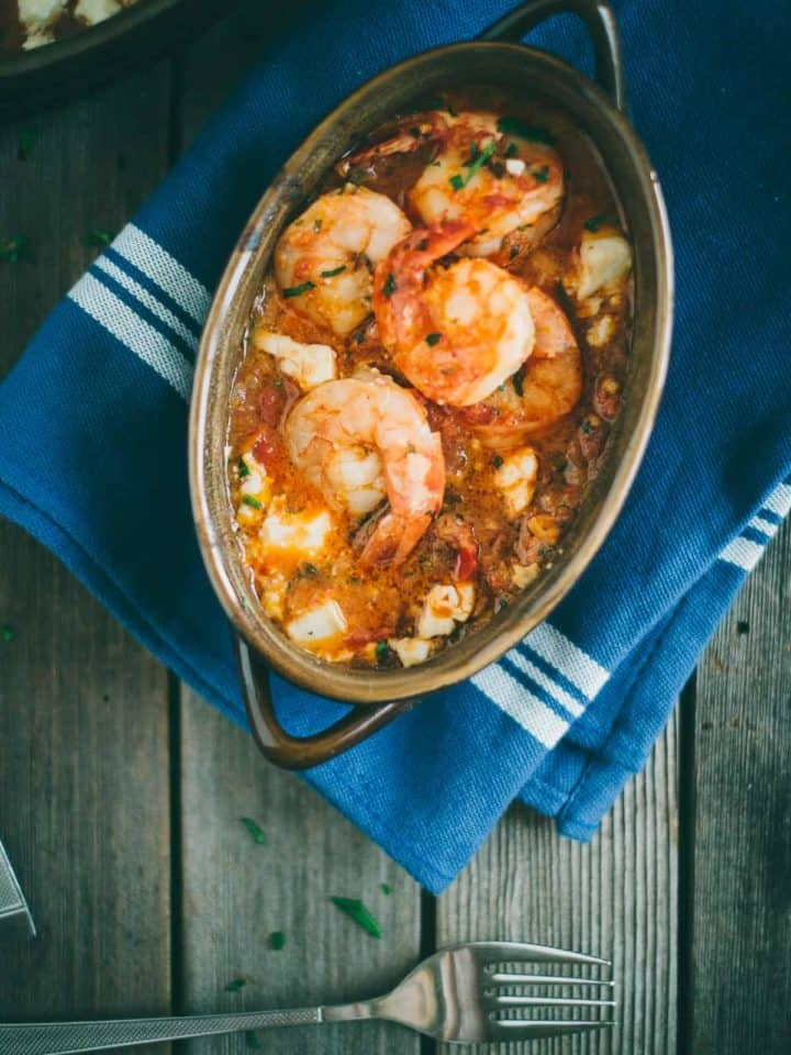 Prawn saganaki served in a claypot dish with ouzo on a wooden table