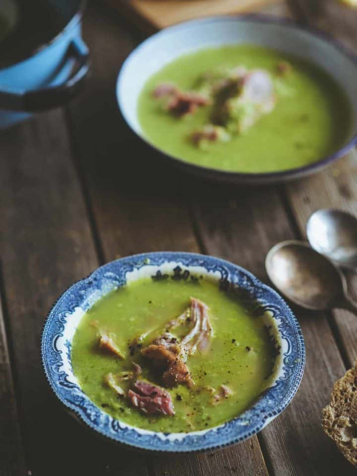 two bowls of homemade pea and ham soup on a rustic table with bread