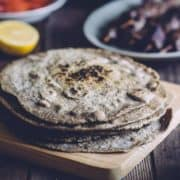 a stack of buckwheat pita bread on a wooden board