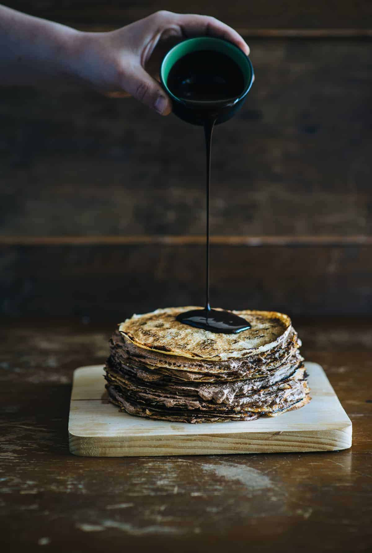 pouring chocolate over Nutella crepe cake