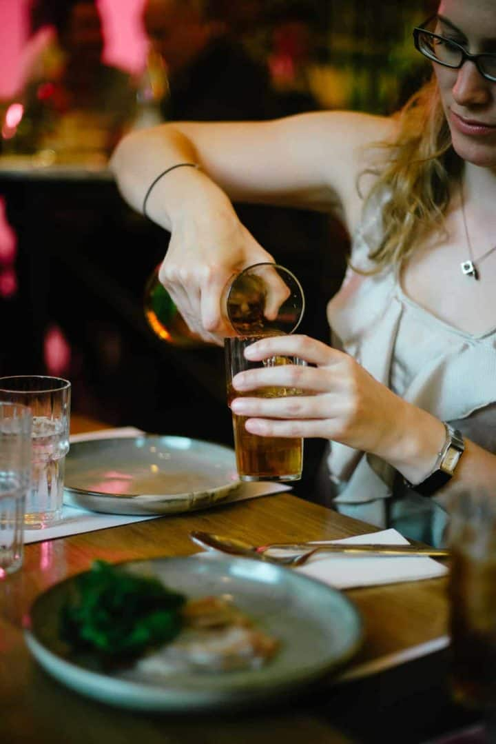 girl pouring herself a drink at restaurant