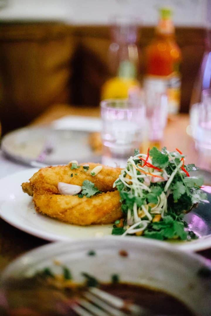 fried fish served on a plate with a colourful side salad