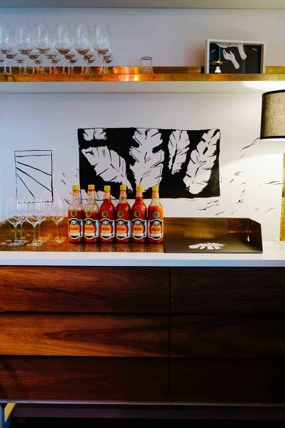 hot sauce bottles all lined up on ca counter at Golden Boy restaurant in Adelaide