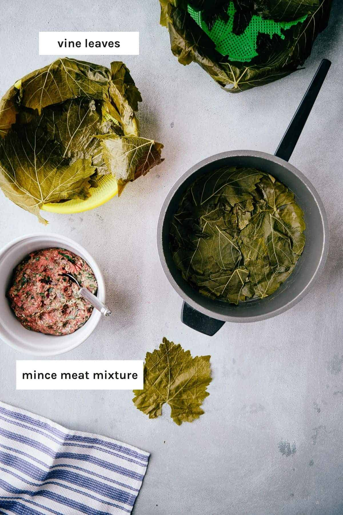 brined vine leaves and ground meat on a grey table