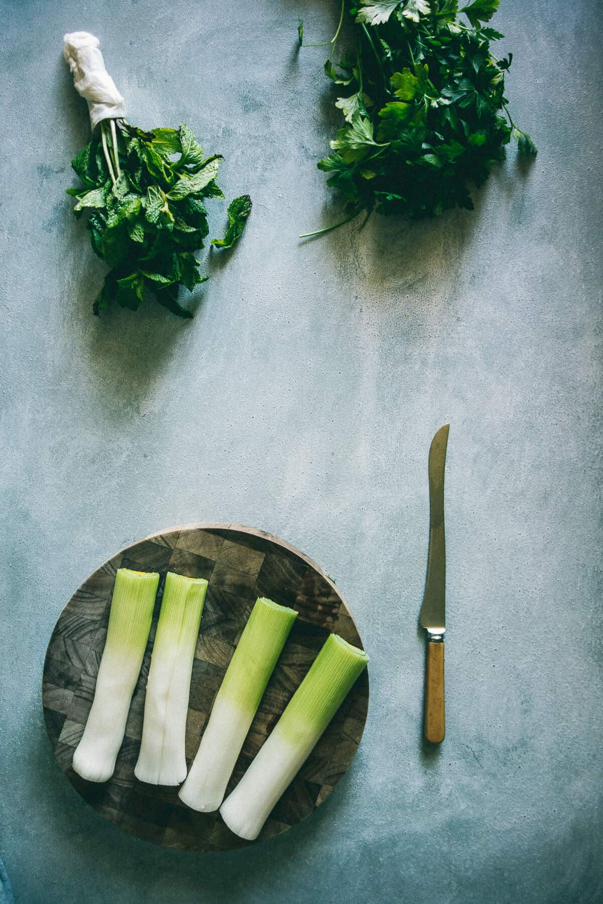 leeks and herbs on a chopping board