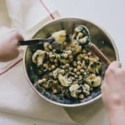 cauliflower and chickpea salad being tosses in a bowl