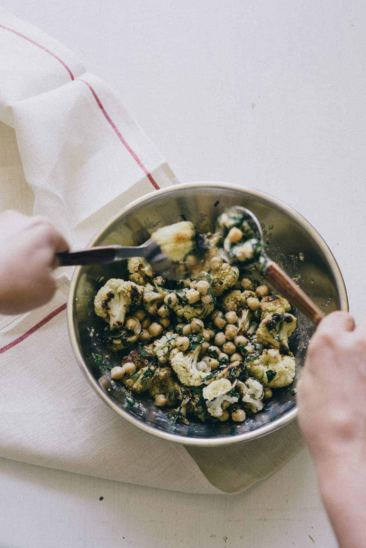 tossing roasted cauliflower chickpea salad in a bowl