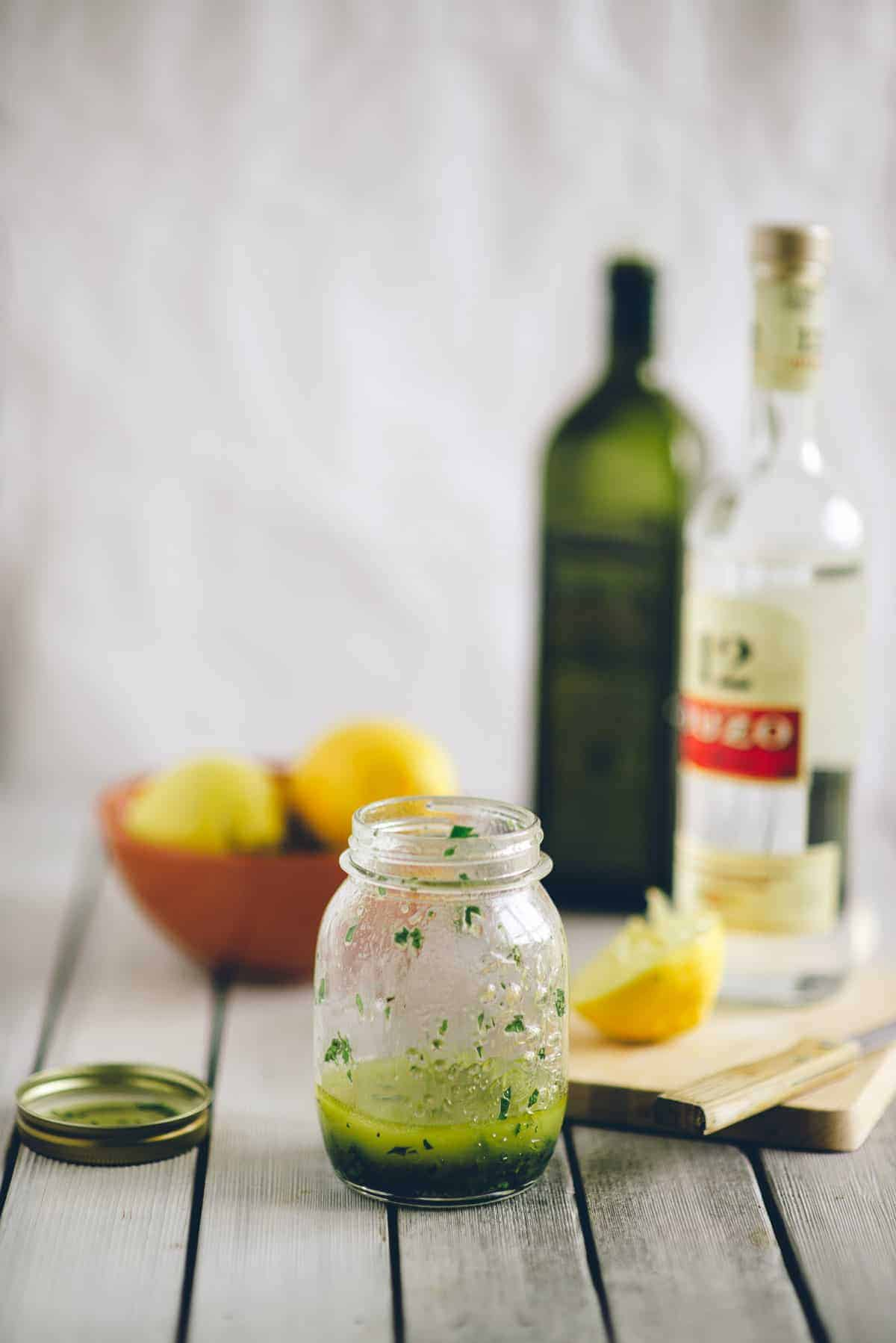 a jar of salad dressing made with ouzo on a white table