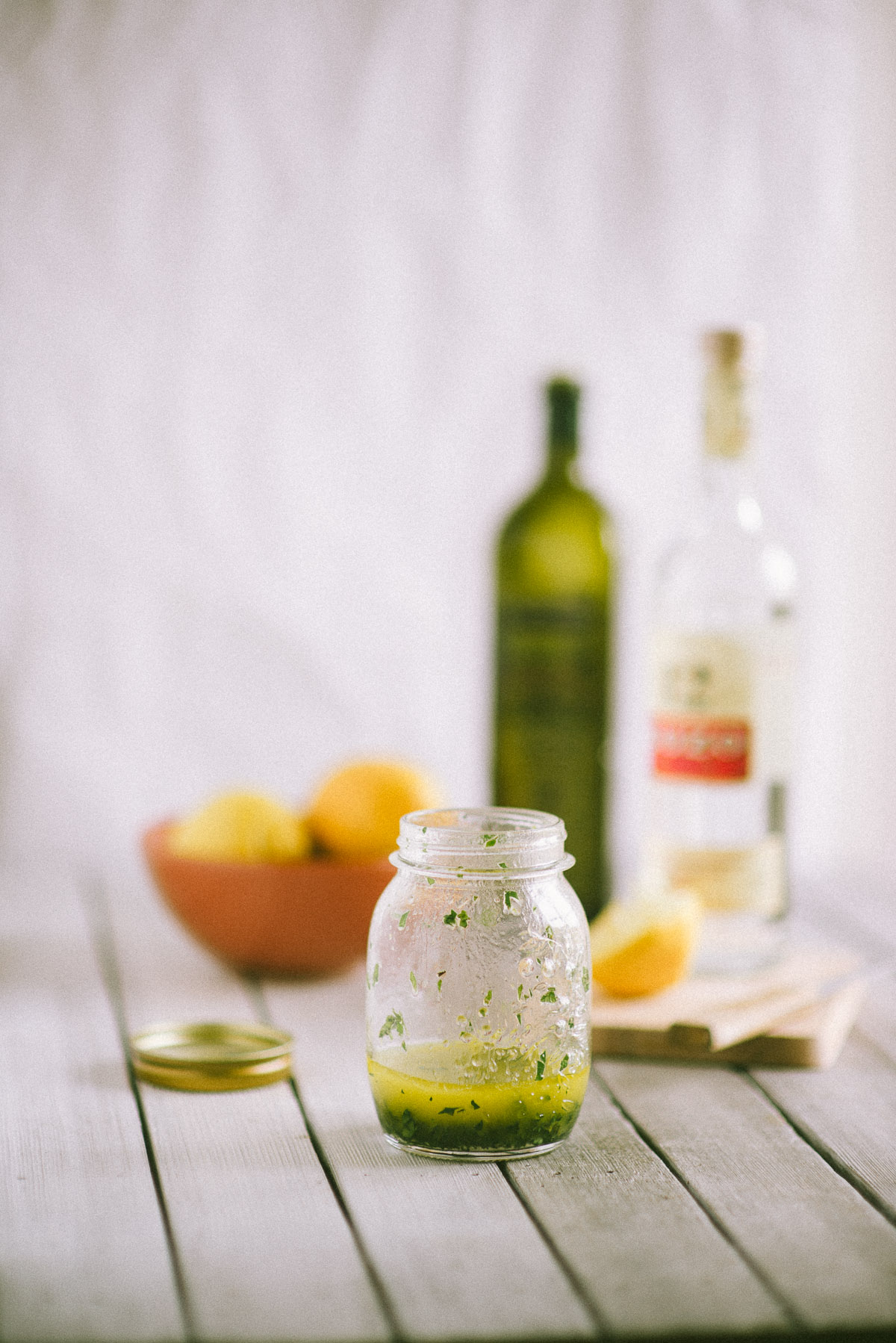 a jar of salad dressing made suing ouzo on a table