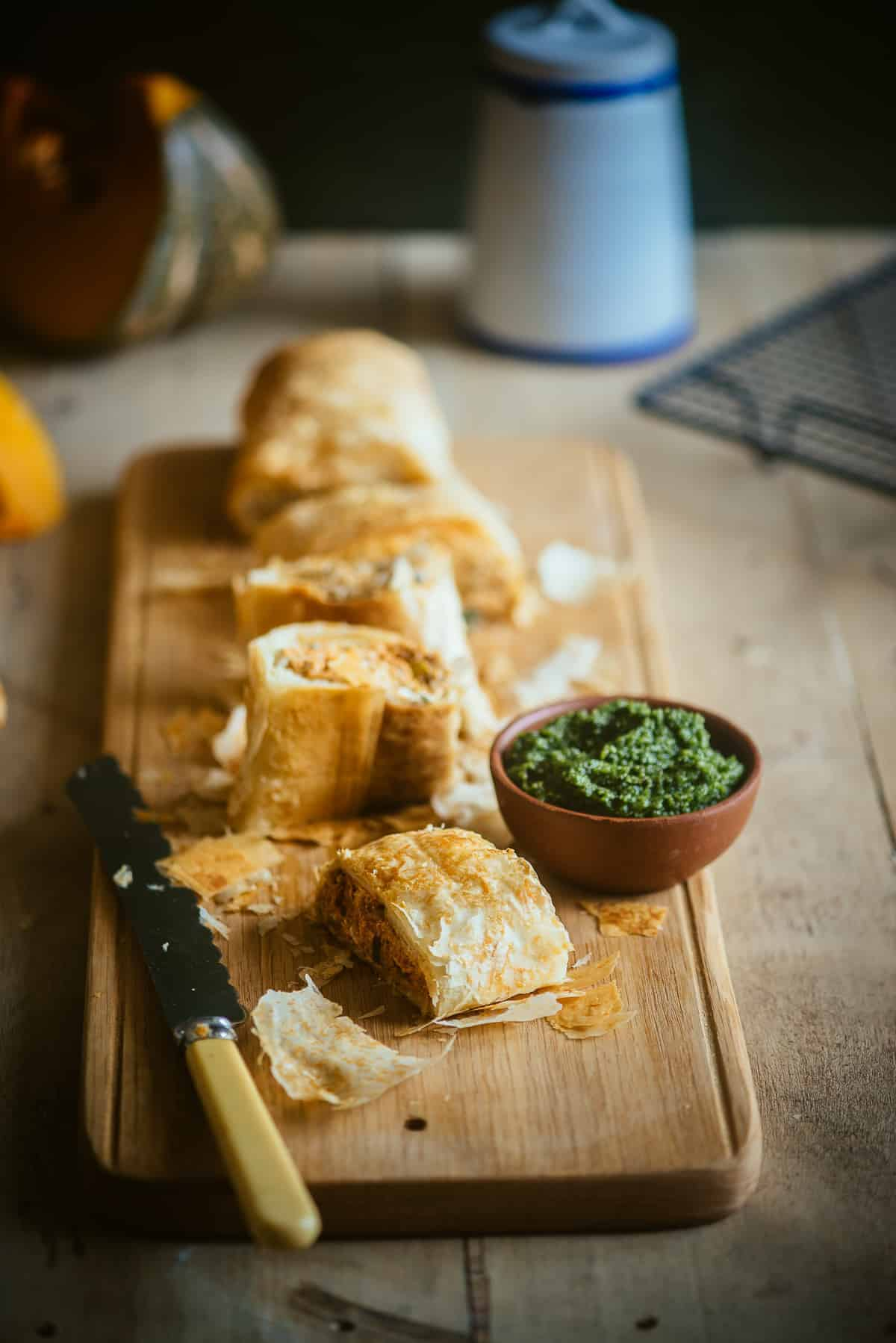 a long fillo roll filled with pumpkin and feta served with a basil pesto