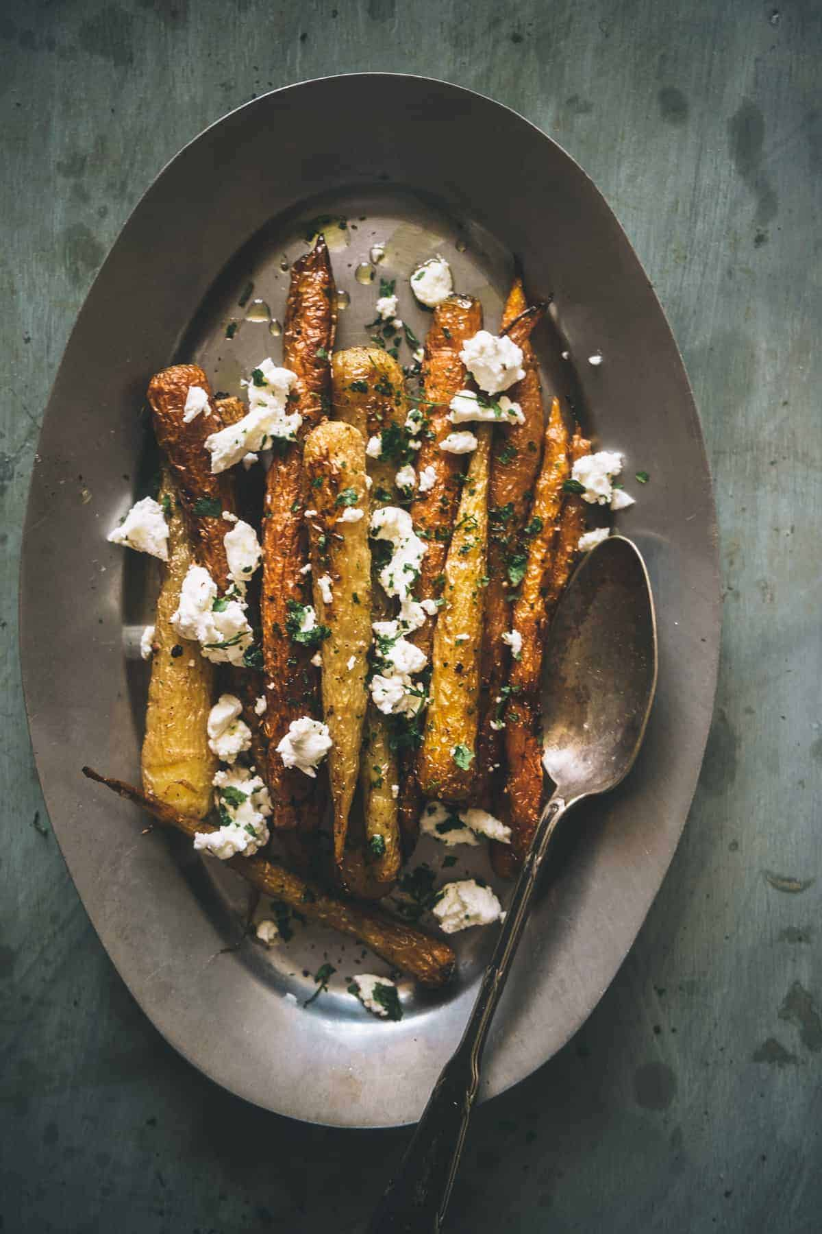 a platter of roasted carrots with ground fennel and topped with goats cheese