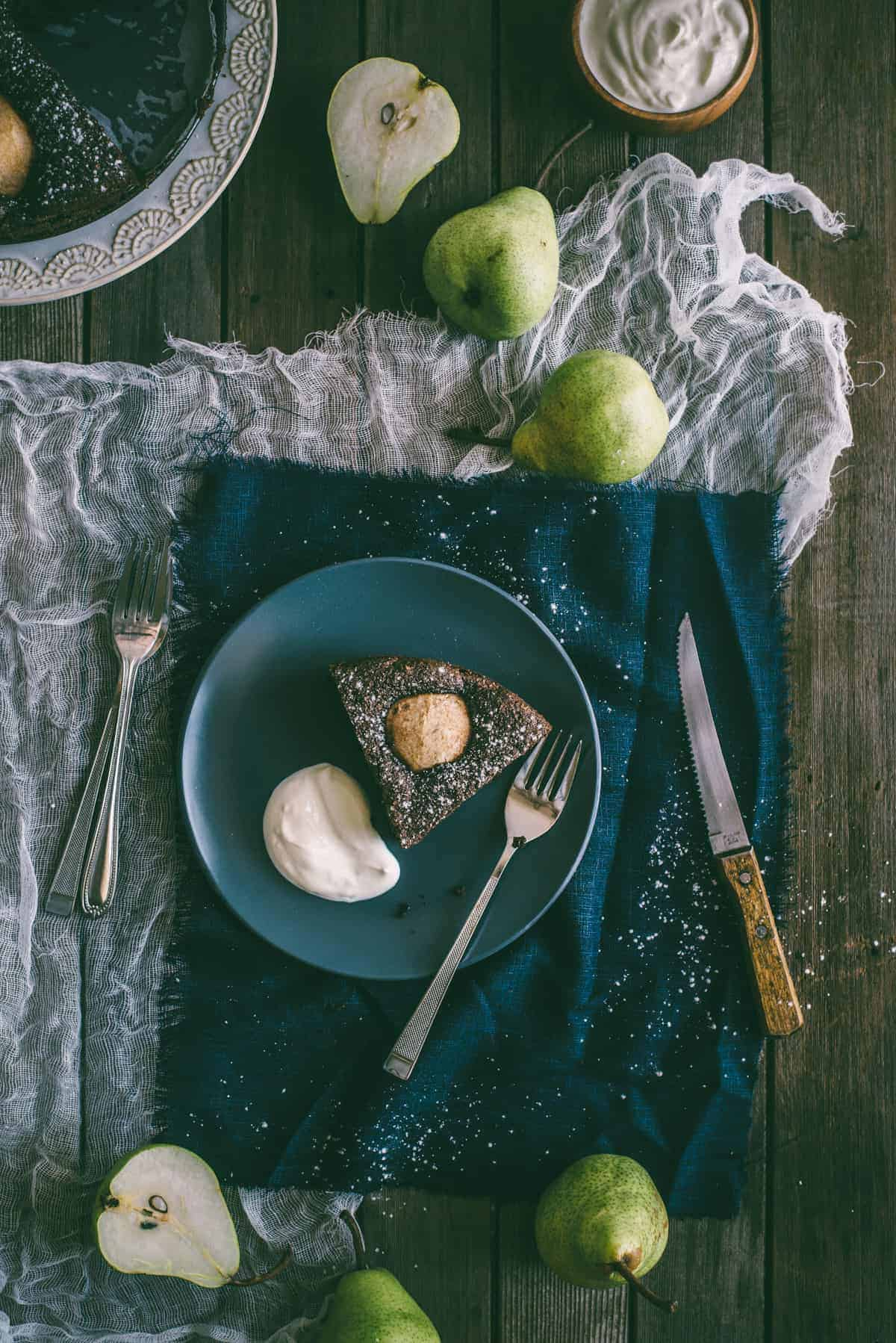 a slice of chocolate and pear cake on a rustic table
